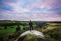 © Licensed to London News Pictures. 20/09/2016. Baildon UK. A man looks out across Shipley from the top of Baildon Moor at dawn this morning. Yorkshire is set for a day of cloud cover & rain later on.  Photo credit: Andrew McCaren/LNP