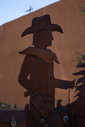 metal cowboy sculpture outdoors by an adobe wall in New Mexico