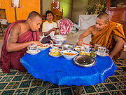 "01 MARCH 2014 - MAE SOT, TAK, THAILAND: A layperson fans Burmese Buddhist monks eating in a temple in a Burmese community in the forest a few kilometers north of Mae Sot. Mae Sot, on the Thai-Myanmer (Burma) border, has a very large population of Burmese migrants. Some are refugees who left Myanmar to escape civil unrest and political persecution, others are ""economic refugees"" who came to Thailand looking for work and better opportunities.    PHOTO BY JACK KURTZ"