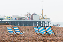**CAPTION CORRECTION. Incorrect date on original picture. Picture taken TODAY 28/05/2016** © Licensed to London News Pictures. 28/05/2016. Brighton, UK. Deckchairs stand unused on a virtually empty beach in Brighton as colder wind and rain is hitting the seaside resort. Photo credit: Hugo Michiels/LNP