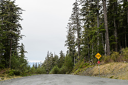 This sign marks the end of the Glacier Highway that currently ends at Echo Cove, approximately 43 miles north of Juneau, Alaska. The Juneau Access Improvements Project is a proposed $570-million road project to extend Glacier Highway for closer access to the southeast Alaska towns of Haines and Skagway. Juneau, Alaska&rsquo;s capital, is the only capital city in the United States whose roads do not connect with the continental road network. Currently travelers either have to fly between Juneau, Haines and Skagway, or travel on one of the Alaska Marine Highway System ferries.<br /> <br /> The plan by Alaska&rsquo;s Department of Transportation and Public Facilities calls for extending the road 48 miles along the Lynn Canal from Echo Cove north of Juneau to the Katzehin River where a new ferry terminal would be built. From there yet-to-be-built smaller ferries would transport vehicles and passengers to Haines and Skagway with four to eight trips per day.<br /> <br /> The proposal, decades in the making, is a contentious issue within the Lynn Canal communities. Proponents cite greater travel flexibility, lower costs for the state and travelers. Opponents cite concerns for marine and terrestrial wildlife, economic loss to local businesses, winter travel safety, landscape degradation, lack of planning for handling walk-on passengers to and from the remote Katzehin terminal and the high cost of the project.<br /> <br /> Most of the $570-million road construction cost will be paid by the federal government, with the state picking up approximately 10 percent in matching costs.<br /> <br /> In July, 2015, Alaska Governor Bill Walker lifted a moratorium on work on the project to complete environmental impact studies.