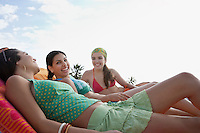 Three teenage girls (16-17) relaxing on sunloungers