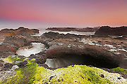 At high tide, Pacific Ocean waves flow under a double lava arch on the coast at Yachats, Oregon.