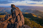 A volcanic rock tower stands watch high on the shoulder of Mt. St. Helena, a 4,341' peak that sits at the Northern end of the Napa Valley in Robert Louis Stevenson State Park. The canyon below feeds the headwaters of the Napa River. To the right, the sun rakes across the Mayacamas Mountains and Sonoma County as it sets to the West over the Pacific Ocean.