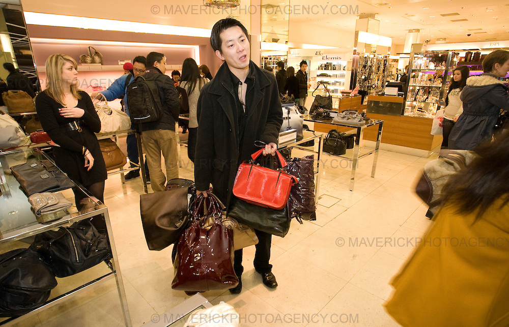 A Shopper stands exhausted clutching handbags in a Harvey Nichols store to take advantage of the Boxing Day Sales.