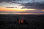 Friends watch the sunset around a campfire on South Beach, near Newport Oregon.
