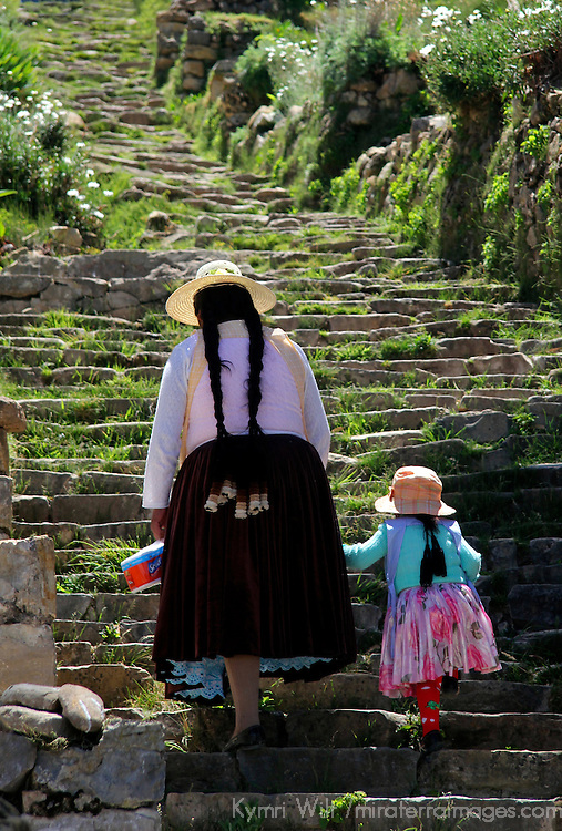 South America, Bolivia, Sun Island. Woman and child climb Incan steps on Isla del Sol.