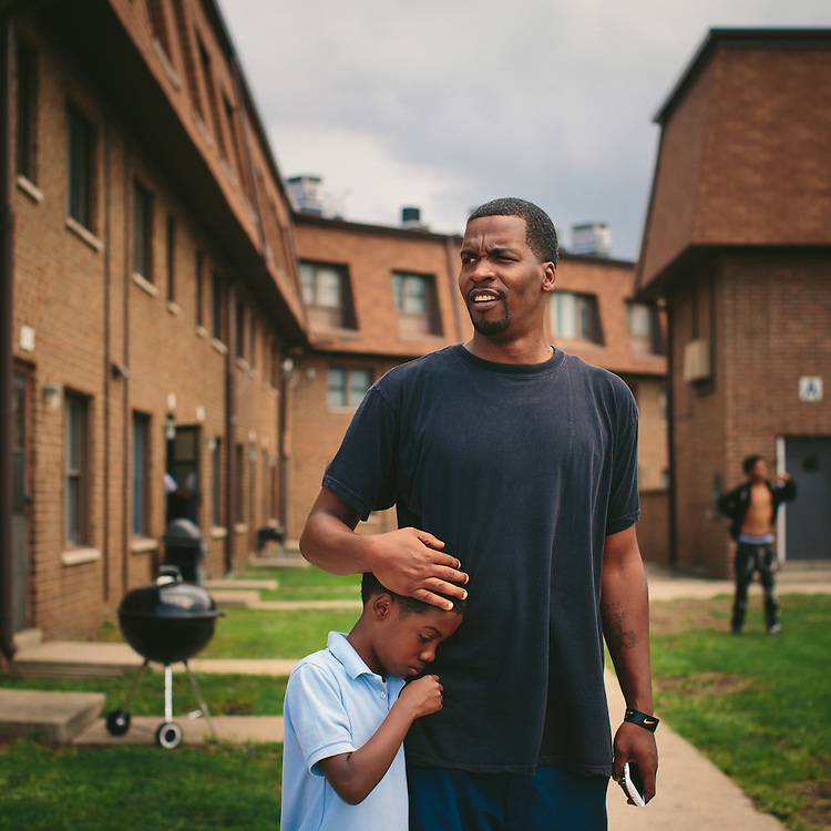 East Chicago, Indiana<br /> <br /> Lamont Anderson embraces his son Lamont Anderson Jr., 8, at the West Calumet Housing Complex. Anderson Jr.'s blood lead levels test results were above the CDC&rsquo;s 5 mg/d threshold for action. After living in the complex for more than a decade, the family moved to Gary, Indiana earlier this summer.<br /> <br /> ||||<br /> <br /> The West Calumet Housing Complex, which is currently home to about 1,200 people, is located on a 79-acre Environmental Protection Agency Superfund site where a USS Lead facility was located in East Chicago, Indiana. Up until 1985, a lead refinery, a copper smelter and a secondary lead smelter were also in the area. The houses were built between the late 1960s and early 1970s.<br /> <br /> East Chicago is zoned close to 80 percent heavy industrial, and the local government relies on the patronage, jobs and tax revenue that the oil and steel industries bring. However, many jobs disappeared when the steel industry modernized and shifted overseas in the late 20th century, leading to extensive job loss for the working class. People there have a long, complicated relationship with industry -- and its environmental legacy will affect generations to come.<br /> <br /> Photo by Alyssa Schukar