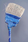 broken broom mended with blue masking tape