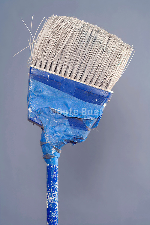 broken broom mended with blue masking tape