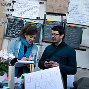 Volunteer activists planning the day ahead. Day three of the occupation - and the first Monday. The Occupy London Stock Exchange movement was formed in London in solidarity with the US based Occupy Wall Street. The movements are a respons and in anger to what is seen by many as corporate greed and a failed banking system being bailed out by the public, - which in return are suffering austerity measures to make up for the billions of lost money. The movement occupied the St Paul's Square in the City of London Sat Oct 15 after it failed to secure and occupy Pator Noster Square and the Stock Exchnage itself.