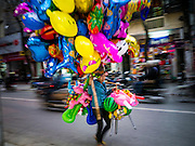31 MARCH 2012 - HANOI, VIETNAM:   A balloon and toy vendor walks down a street in the Old Quarter of Hanoi, Vietnam.  PHOTO BY JACK KURTZ