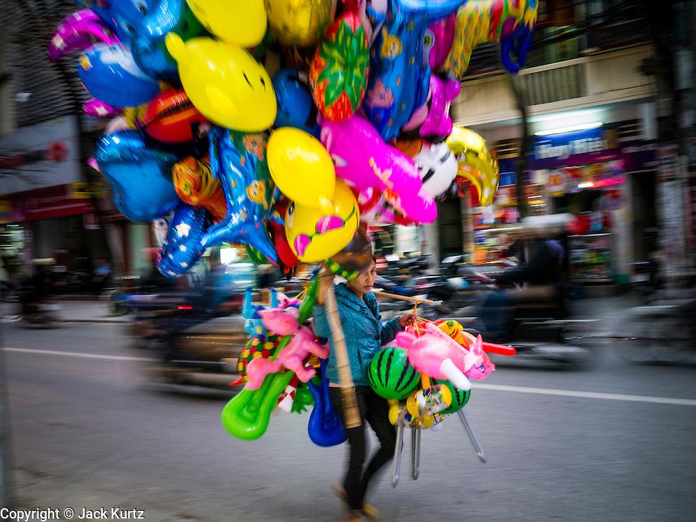 31 MARCH 2012 - HANOI, VIETNAM:   A balloon and toy vendor walks down a street in the Old Quarter of Hanoi, Vietnam.  PHOTO BY JACK KURTZ