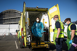 © Licensed to London News Pictures . 21/04/2020. Manchester, UK. A paramedic wearing a mixture of type 2 and type 3 PPE steps from an ambulance after delivering a patient with Coronavirus to the Nightingale Hospital . Cleaners employed to deep clean the ambulance wait to step on board to clean the vehicle . The National Health Service has built a 648 bed field hospital for the treatment of Covid-19 patients , at the historical railway station terminus which now forms the main hall of the Manchester Central Convention Centre . The facility is treating patients from across the North West of England , providing them with general medical care and oxygen therapy after discharge from Intensive Care Units . Photo credit : Joel Goodman/LNP
