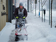 17 JANUARY 2020 - DES MOINES, IOWA: A worker uses a snowblower to clear a path on a snow packed sidewalk in the Court District of Des Moines. The second significant snow fall in a week hit central Iowa Friday. The snow started falling during the morning rush hour and by early afternoon about five inches had fallen in Des Moines. Meteorologists said up to 1/10 of an inch of ice could cover the snow by the end of the day. The snowstorm was expected to turn into a blizzard in northern Iowa on Saturday with wind speeds above 30MPH. Many businesses in the Des Moines area closed early Friday and several of the Democratic presidential candidates cancelled their campaign events because of the snow.     PHOTO BY JACK KURTZ