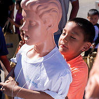 Leland Hughte, 8, learns how to give the heimlich maneuver at the 6th Annual Preparedness and Public Safety Day, Saturday at the Rio West Mall.