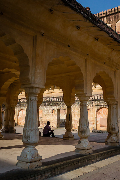 A man waits, sitting in one of the many courtyards in the Amber Palace, near Jaipur