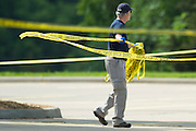 An FBI agent removes tapes from the crime scene outside of the Curtis Culwell Center in Garland, Texas on May 4, 2015.  (Cooper Neill for The New York Times)