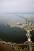 Nederland, Friesland, Gemeente Wonseradeel, 28-04-2010; Afsluitdijk ter hoogte van Kornwerderzand, gezien naar de kust van Friesland. Op het voormalig werkeiland liggen de Lorentzsluizen, een complex van spuisluizen en schutsluizen. De spuisluizen (uitwaterende sluizen lozen van het IJsselmeer op de Waddenzee (li). De sluizen worden beschermd door kazematten (bunkers). .Enclosure Dam at the height of Kornwerderzand seen in the direction of the coast of Friesland. On teh former work island the Lorentz locks, a complex of sluices and locks. The sluices sluice surplus water to the Wadden sea (l). The locks are protected by bunkers..luchtfoto (toeslag), aerial photo (additional fee required).foto/photo Siebe Swart
