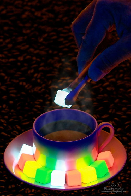 Sugar tongs holding a cube of glowing sugar over a cup of coffee.Black light