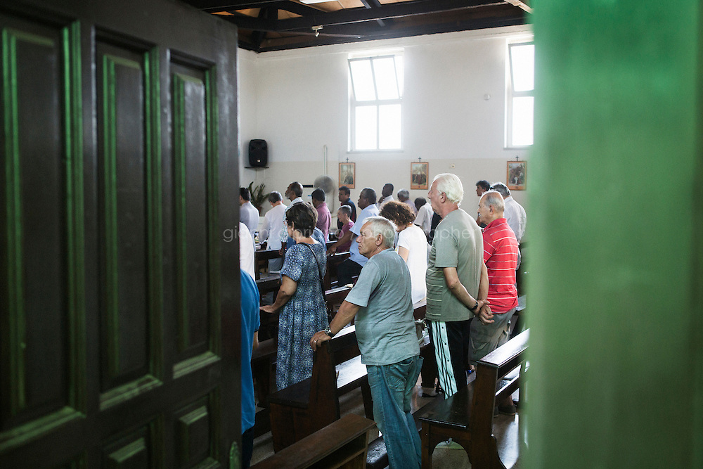 ROME, ITALY - 26 AUGUST 2016: Homeless men and volunteers attend mass in the chapel of Casa Serena, a prefabricated house for homeless men in Rome, Italy, on August 26th 2016.<br /> <br /> Casa Serena, inaugurated in 1993, hosts approximately 70 men, 50 years or above, of any nationality, religion, colour. <br /> <br /> The Missionaries of Charity-Contemplative is a diocesan religious Institute composed of Brothers and priests with equal rights and obligations, founded by Blessed Teresa of Calcutta with Fr. Sebastian Vazhakala in 1979. The members take public vows of Chastity, Poverty, Obedience and free service to the poor.<br /> <br /> Mother Teresa, also known as Blessed Teresa of Calcutta, was an Albanian Roman Catholic nun and missionary. She founded the Missionaries of Charity, a Roman Catholic religious congregation, whose members must adhere to the vows of chastity, poverty, and obedience, as well as the vow to give wholehearted free service to the poorest of the poor. Shortly after she died in 1997, Pope John Paul II waived the usual five-year waiting period and allowed the opening of the process to declare her sainthood. She was beatified in 2003. A second miracle was credited to her intercession by Pope Francis, in December 2015, paving the way for her to be recognised as a saint by the Roman Catholic Church. Her canonisation is scheduled for September 4th 2016, a day before the 19th anniversary of her death.