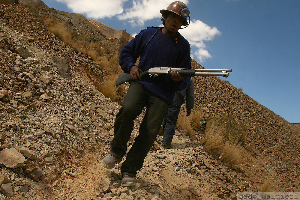 A state-employed miner carries a gun and shouts to his coworkers to keep defending their facility in the city of Huanuni, some 290 kilometers south of capital La Paz, Bolivia on Friday, Oct. 6, 2006. The Bolivian government is sending 700 additional police to the quell a clash between rival bands of miners over one of South America's richest tin mines. Officials say at least 11 people have been killed and more than 50 injured.There were no reports of renewed conflict Friday, but both sides continued to detonate dynamite and homemade explosives, with the blasts echoing across the barren mountain looming above this small mining town 290 kilometers (180 miles) south of the capital of La Paz.(AP Photo/Dado Galdieri)