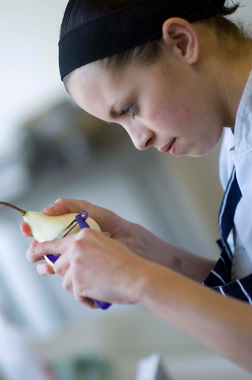 Chef peels a pear in the kitchen of Fishmore Hall, Ludlow