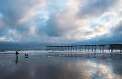 © Licensed to London News Pictures. 10/03/2014<br /> <br /> Saltburn, Cleveland, United Kingdom<br /> <br /> A woman walks her dog along the beach at first light in Saltburn by the Sea in Cleveland.<br /> <br /> Photo credit : Ian Forsyth/LNP