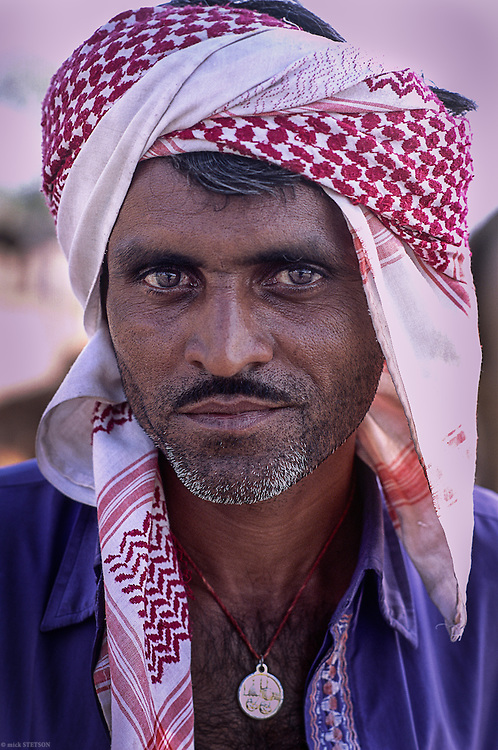 — A camel herdsman attending a local camel fair has ethnic roots that possibly originate in Iran or Central Eurasia and of Scythian ancestry. The turban he's wearing is like the Arabic kufiya.