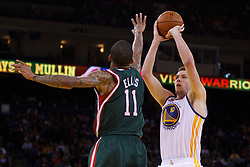 Mar 16, 2012; Oakland, CA, USA; Golden State Warriors power forward David Lee (10) shoots over Milwaukee Bucks point guard Monta Ellis (11) during the fourth quarter at Oracle Arena. Milwaukee defeated Golden State 120-98. Mandatory Credit: Jason O. Watson-US PRESSWIRE
