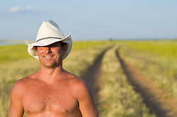 Shirtless cowboy smiling in sunlight on a grass lined dirt road in Las Vegas, NM