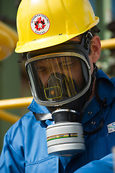 Chemist Thomas Pauwels, wears a gas mask as he takes samples of liquid chlorine at the Solvay SA chemical plant in Antwerp, Belgium, on Thursday, April 22, 2010. Since the boiling point of liquid chlorine is minus 34.1 degrees Celsius, (-34.1 °C) the glass tubes containing the samples are submerged in dry ice.  Solvay SA is the world's largest supplier of Soda Ash or Sodium Carbonate and is also a major producer of caustic soda, hydrogen peroxide, chlorine and fluorinated products. (Photo © Jock Fistick)