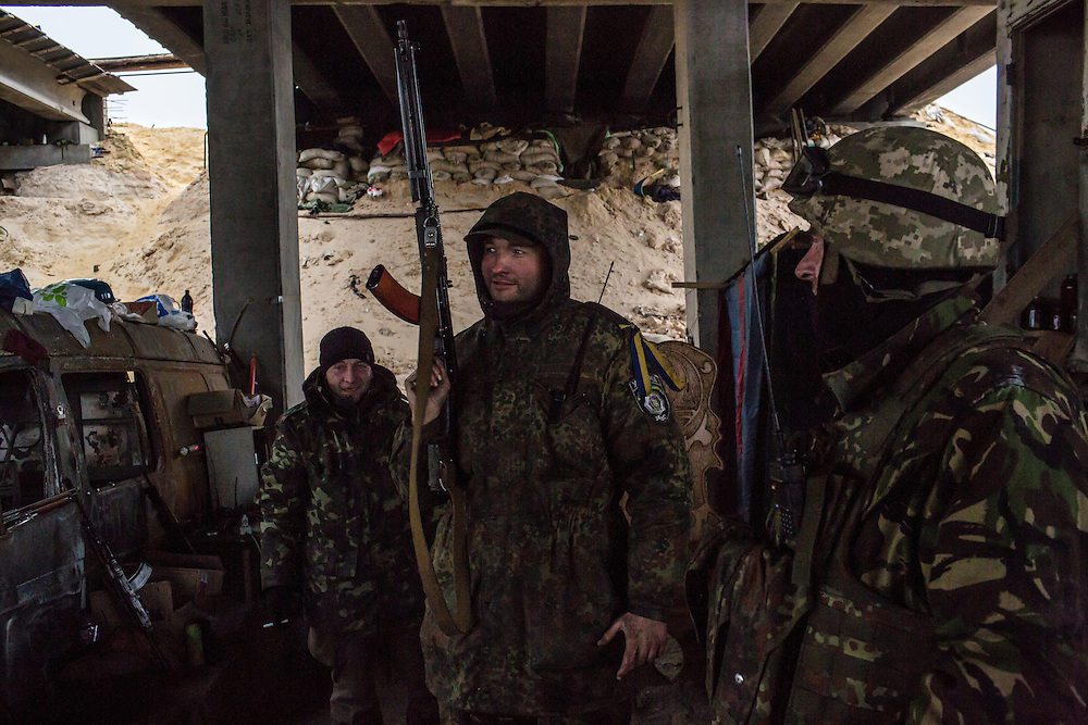 PERVOMAISKE, UKRAINE - NOVEMBER 17, 2014: Skala, center, and other members of the 5th platoon of the Dnipro-1 brigade, a pro-Ukraine militia, at their post underneath a bridge in Pervomaiske, Ukraine. CREDIT: Brendan Hoffman for The New York Times
