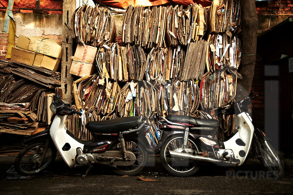 Cardboard recycling shop with two motorbikes parked in front of. Vietnam, Asia