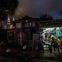 Residents get their haircut at night at a street barber shop in Kampung Baru, Kuala Lumpur, Malaysia, 18 April 2017.