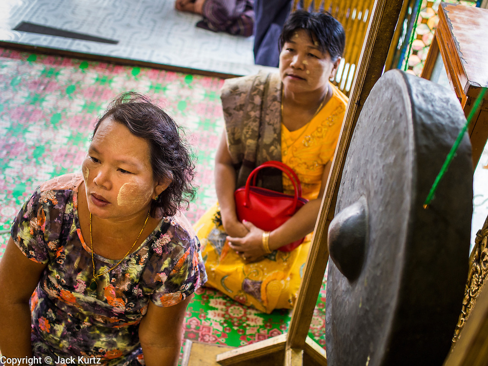 04 JUNE 2014 - YANGON, YANGON REGION, MYANMAR: Women pray in Botataung Paya (Pagoda) in Yangon, Myanmar (Rangoon, Burma). Botataung is one of the most famous pagodas in Yangon with maze like interior of gold leaf covered walls. The pagoda houses a hair from the Buddha and is one of the most sacred sites in Burma. Yangon, with a population of over five million, continues to be the country's largest city and the most important commercial center.     PHOTO BY JACK KURTZ