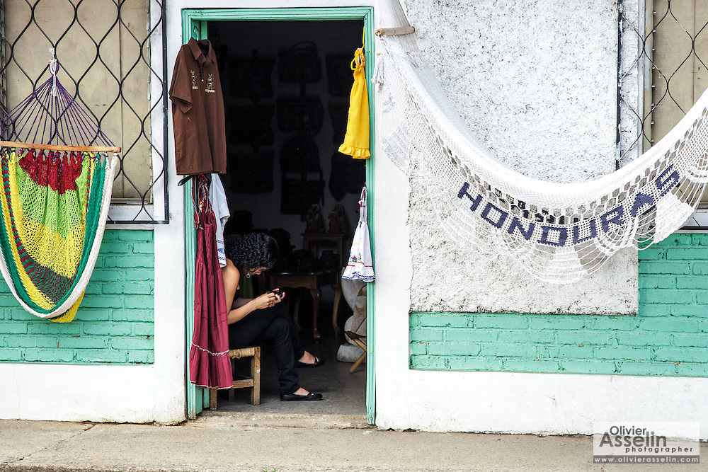 A woman checks her phone while waiting for customers inside a gift shop in the town of Valle de Angeles, Honduras on Friday April 26, 2013.