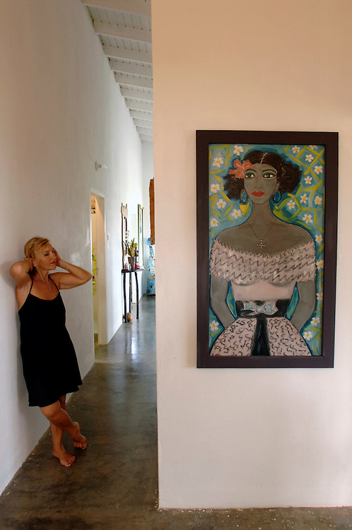 """Trinidad & Tobago, Tobago, Black Rock..German artist Nini Lorenza, who was born in Hamburg, Germany, in 1941,  in her house in Black Rock, Tobago. She has lived in this Caribbean island for 15 years..Nini Lorenza's quote: """"Tobago is such a pretty place I thought I want to be burried right here, so I built my coffin from paper mache and slept on the top, using it as a bed. Then I made all my furniture colourful and very comfortable, all from paper mache. A bar on wheels rolling all over the place for the 'happy hour' any time. I made mirrors, lamps, and the neccessary paintings for the walls. Shopping for luxury pretty things is my favorite addiction. I love thriftshops, hunting for extravagant jewellery, handbags, shoes, cocktail dresses, if they don't fit me, I transform them into art objects. I do what I like."""" . German: Karibik, Kunst, die deutsche Kuenstlerin Nini Lorenza , 1941 in Hamburg beboren, in ihrem Haus in Black Rock, Tobago. Sie lebt seit 15 Jahren auf der Karibikinsel."""