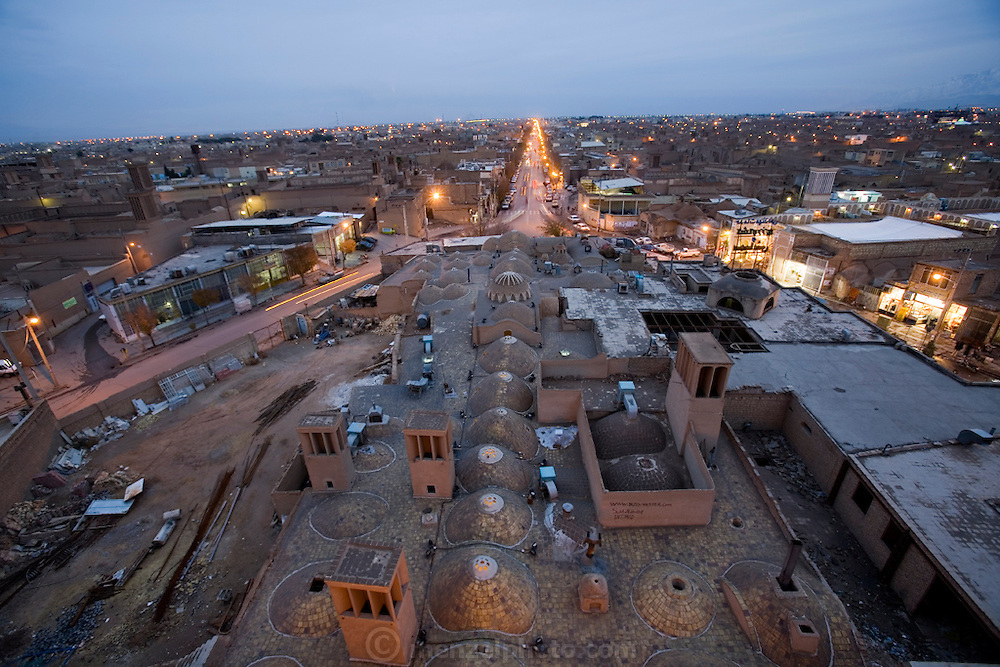 A view of the rooftop of Amir Chakhaq Complex in the city of Yazd, Iran from its highest point at dusk. Windtowers called badgirs (Farsi), seen jutting out of the top of the roof, catch the wind and cool the building. The domes are called gonbads.