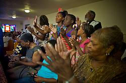 Aliysha Winters, 31, prays in church in  River Rouge, Detroit, Michigan August 12, 2012.