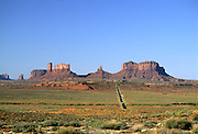 Monument Valley red sandstone formations, narrow road leading to them, Route 163