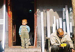 "China, Beijing, 2008. A boy surveys his ""hutong,"" or traditional neighborhood. These low-slung communities are fast disappearing, as streets are widened, and concrete and steel construction replaces bricks in cities all over China.."