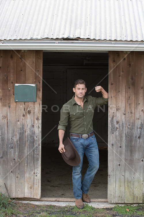 cowboy holding his cowboy hat on a ranch
