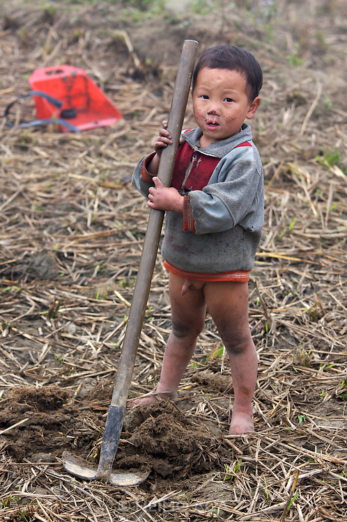 Hilltribe villages around Sapa. Black Hmong boy pretending/playing to work in a paddy field.