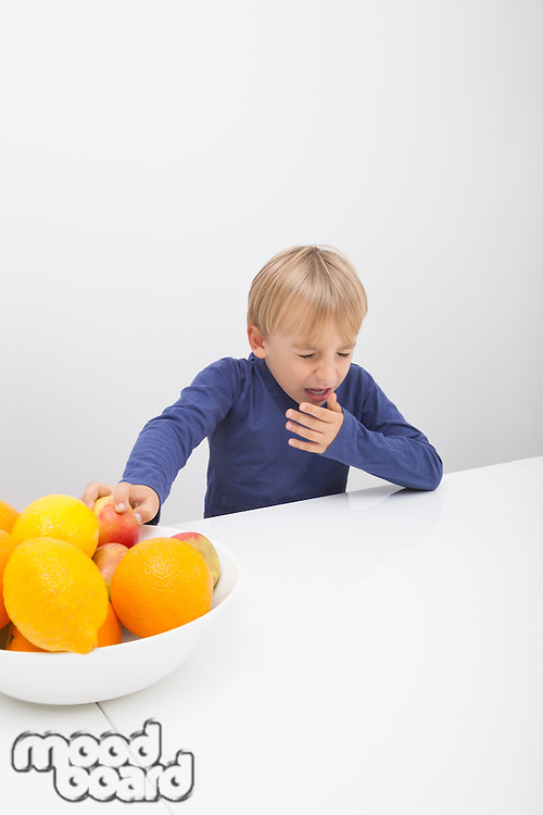 Boy with fruit bowl sneezing at table