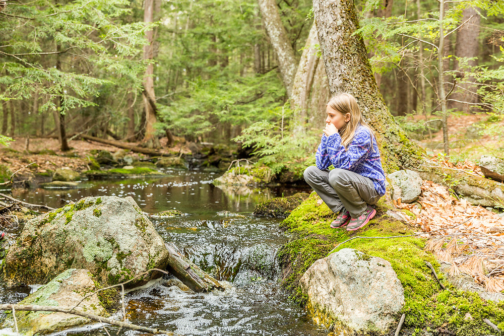 A girl sits next to a small stream in the Stonehouse Forest in Barrington, New Hampshire.