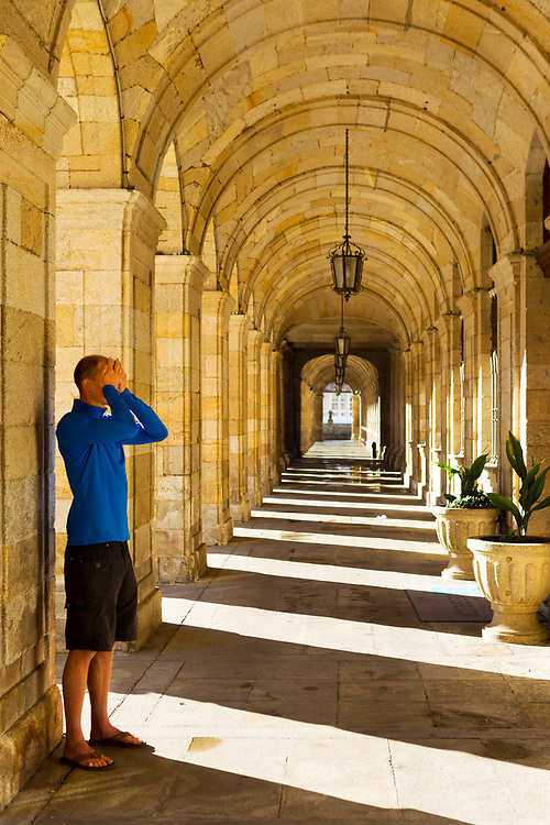 SANTIAGO DE COMPOSTELA, SPAIN - 10th October 2017 - A pilgrim prays at the Praza do Obradoiro main square and Town hall in Santiago de Compostela after walking the Camino de Santiago (Way of St. James), Galicia, Spain.