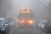 © Licensed to London News Pictures. 11/12/2013. London, UK. A bin lorry uses all its light to make itself visible in the foggy streets. Fog along the banks of the River Thames in Hammesmith, West London this morning 11th December 2013 . Photo credit : Stephen Simpson/LNP