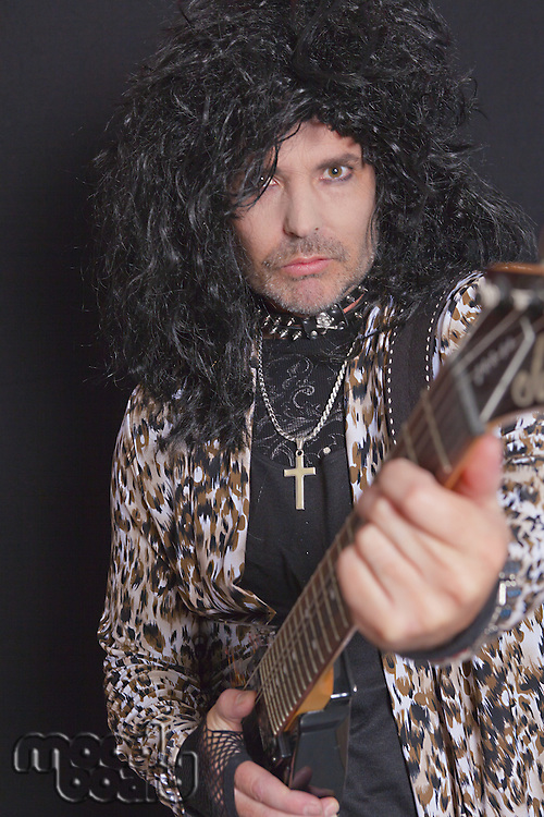 Portrait of middle-aged man wearing leopard skin pattern with guitar over black background
