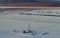 Stock photo of the aerial view of an on-shore rig in a snow covered field